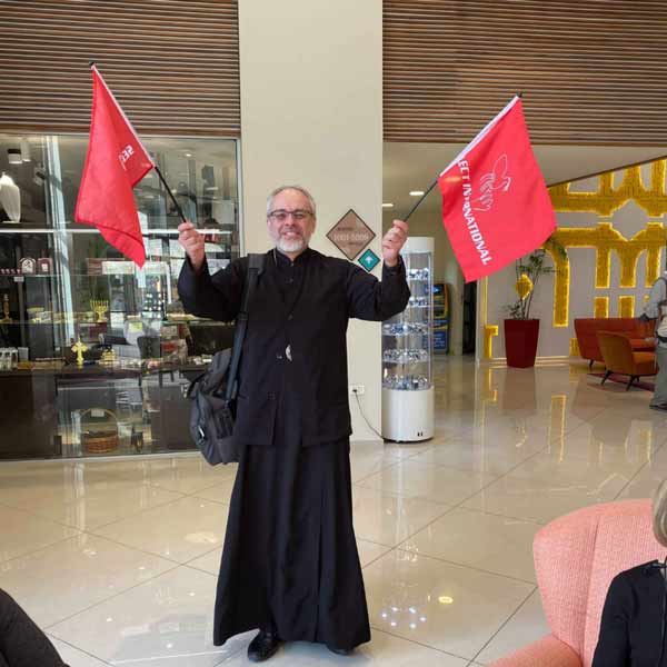 Priest with Select International Tours Flags